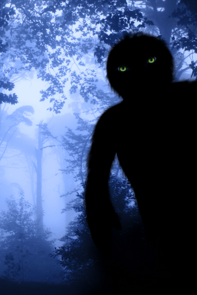 A big black Bigfoot with green eyes in a foggy forest.